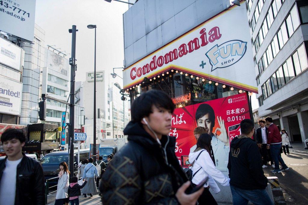 Des piétons passent devant un magasin de préservatifs Condomania dans le quartier de Harajuku à Tokyo en février 2018.