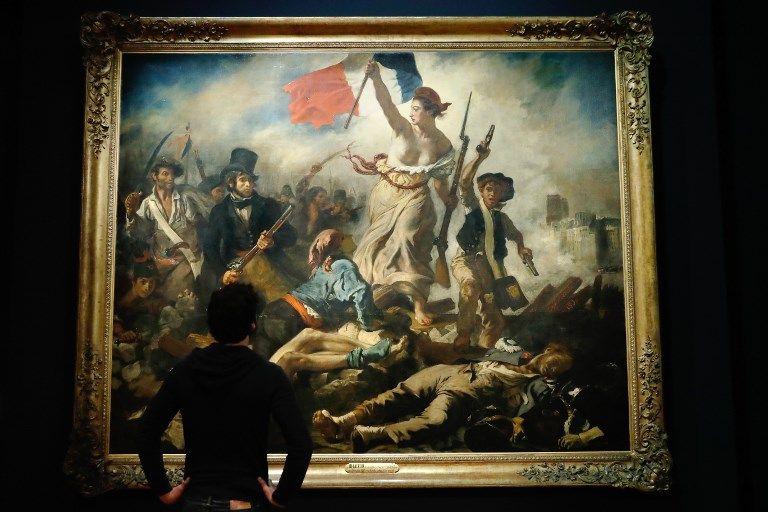 """Un homme regarde le tableau """"La liberté guidant le peuple"""" lors d'une visite de l'exposition """"Delacroix (1798-1863)"""" au musée du Louvre à Paris le 27 mars 2018."""