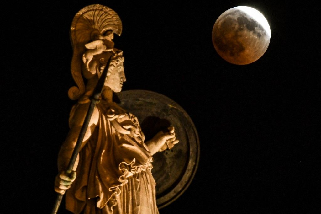 Une photo de la pleine lune à côté d'une statue de la déesse grecque Athéna dans le centre d'Athènes le 27 juillet 2018.