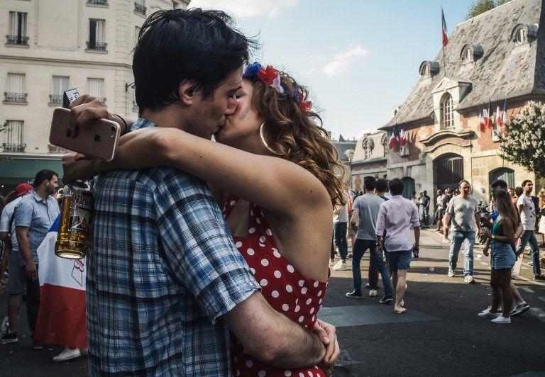 Un couple s'embrasse dans la rue.