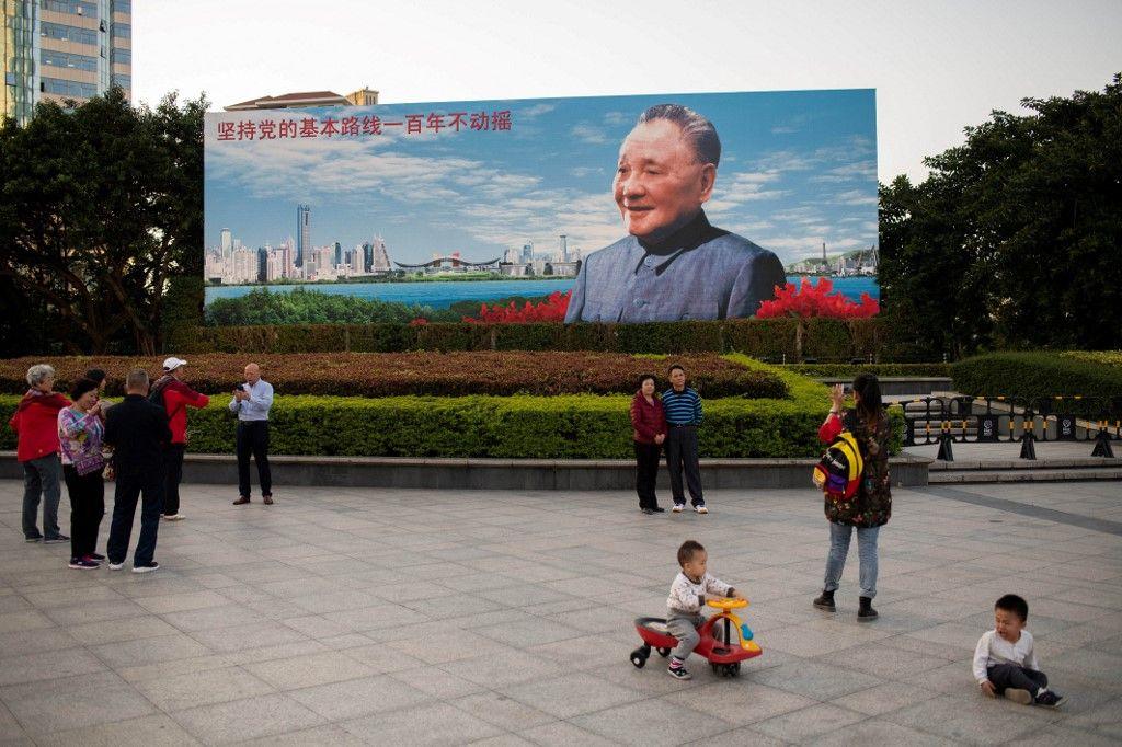 """Des habitants se tiennent devant un panneau d'affichage représentant Deng Xiaoping à la veille du 40e anniversaire de la politique de """"réforme et d'ouverture"""" du pays à Shenzhen, le 17 décembre 2018."""