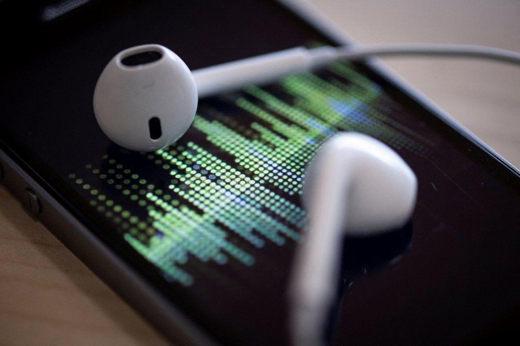 Une photographie montre un smartphone et des écouteurs alors qu'un podcast audio est en cours de lecture.