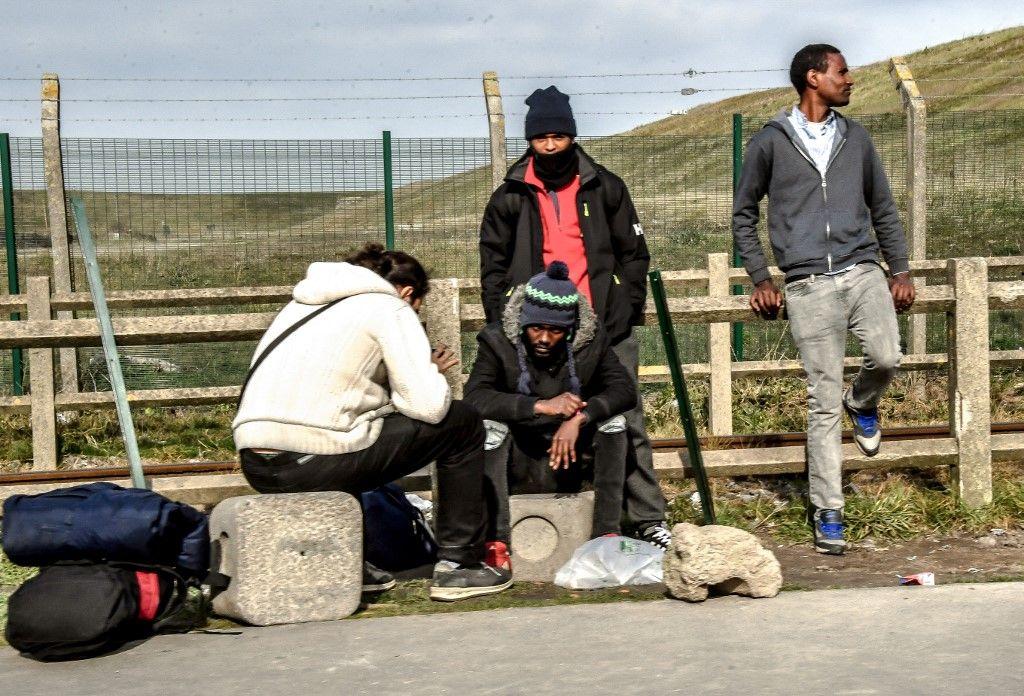 Des migrants s'assoient à proximité de leur camp de fortune non loin de la ville de Calais, dans le nord de la France, le 18 février 2019.