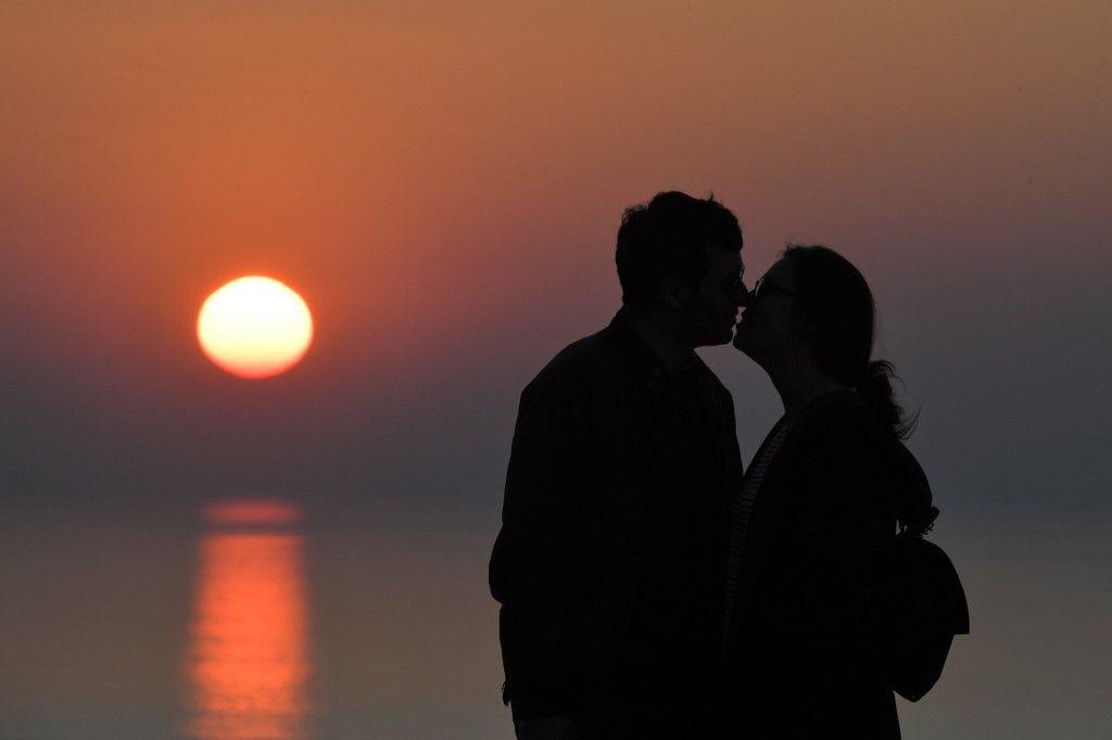 Un couple s'embrasse devant un soleil couchant.