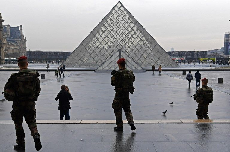 Des militaires de la force Sentinelle patrouillent devant le Musée du Louvre, à Paris.
