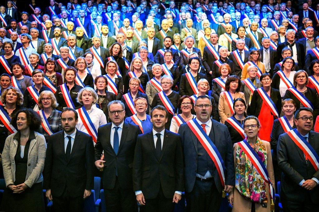 Le chef de l'Etat, Emmanuel Macron, entouré des maires de France, lors d'un congrès