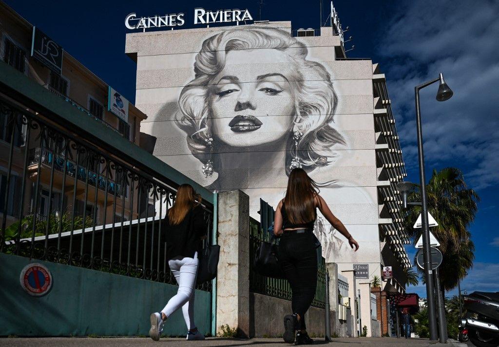 Des piétons passent devant une peinture murale de l'actrice Marilyn Monroe, le 13 mai 2019, à la veille de l'ouverture du 72e Festival de Cannes.