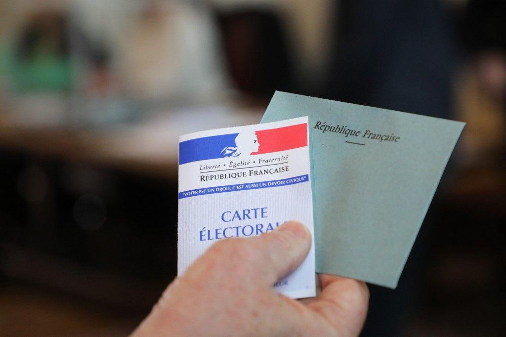 Un électeur s'apprête à voter grâce à sa carte électorale et avec sa carte d'identité.