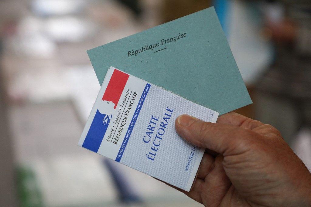 Une personne tient sa carte d'électeur et une enveloppe pour voter pour les élections européennes dans le bureau de vote de la mairie du Touquet, le 26 mai 2019.