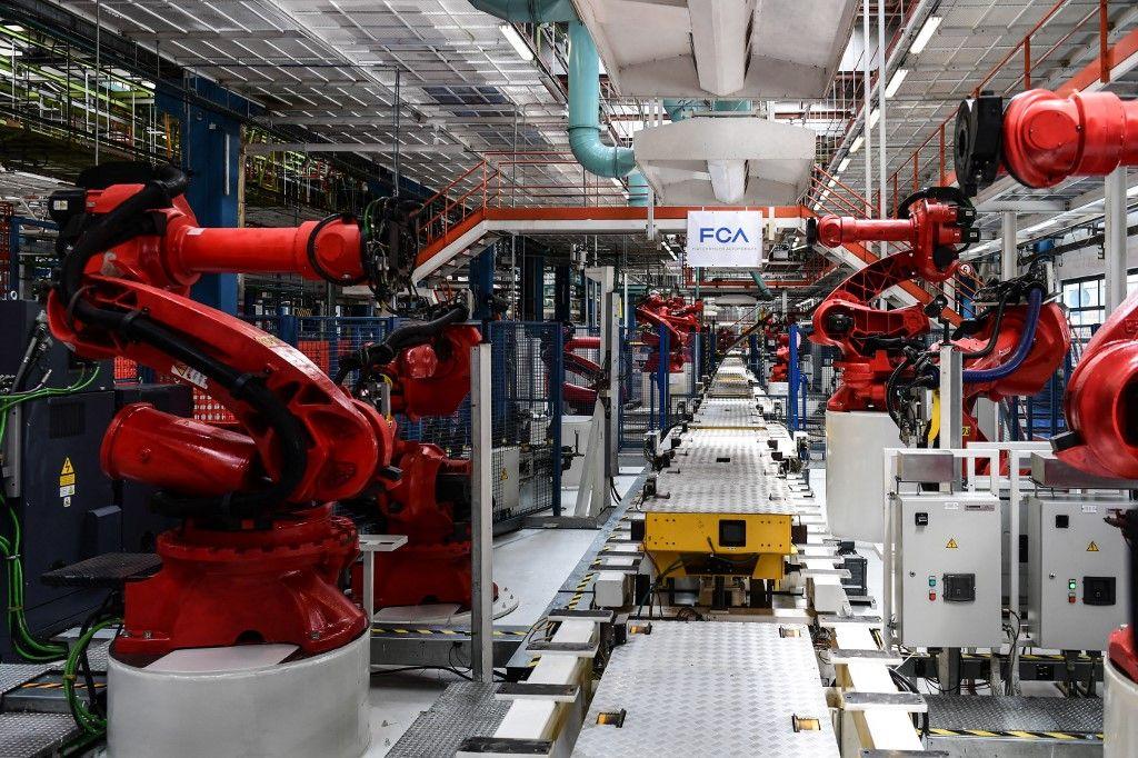 Des robots fabriqués par Comau sur la chaîne de montage du véhicule électrique Fiat 500 BEV, à l'usine Fiat Chrysler Automobiles à Turin en juillet 2019.