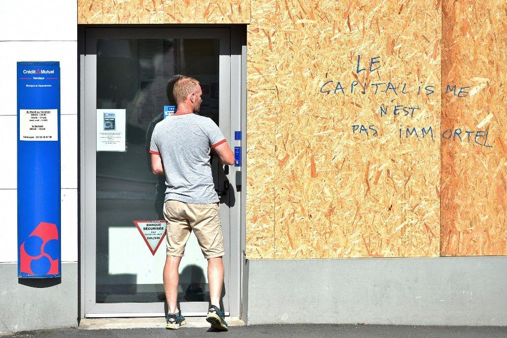 """Un homme regarde un message indiquant """"Le capitalisme n'est pas immortel"""" sur un panneau protégeant une agence bancaire à Hendaye en août 2019 avant le sommet du G7 à Biarritz, du 24 au 26 août 2019."""
