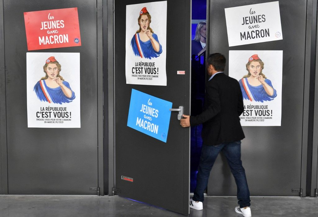 Un homme ouvre une porte avec des affiches de campagne de La République en marche et des Jeunes avec Macron le 7 septembre 2019 à Bordeaux alors qu'il entre dans un rassemblement du parti.