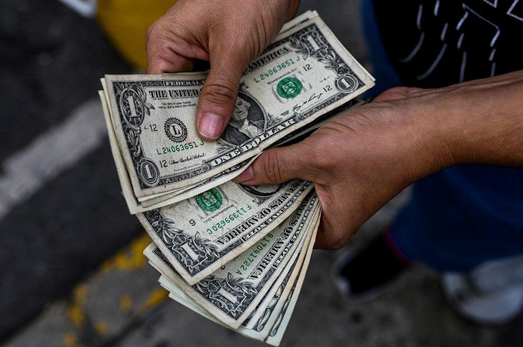 Une personne compte des dollars dans une rue de Caracas le 19 novembre 2019.