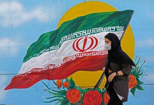 Une Iranienne marche devant une fresque à Téhéran.