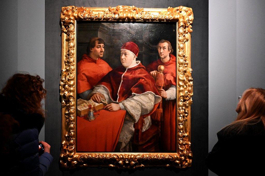 """Des visiteurs regardent le tableau """"Portrait du pape Léon X avec les cardinaux Giulio de Médicis et Luigi de Rossi"""" du peintre Raphaël, le 4 mars 2020, à Rome."""