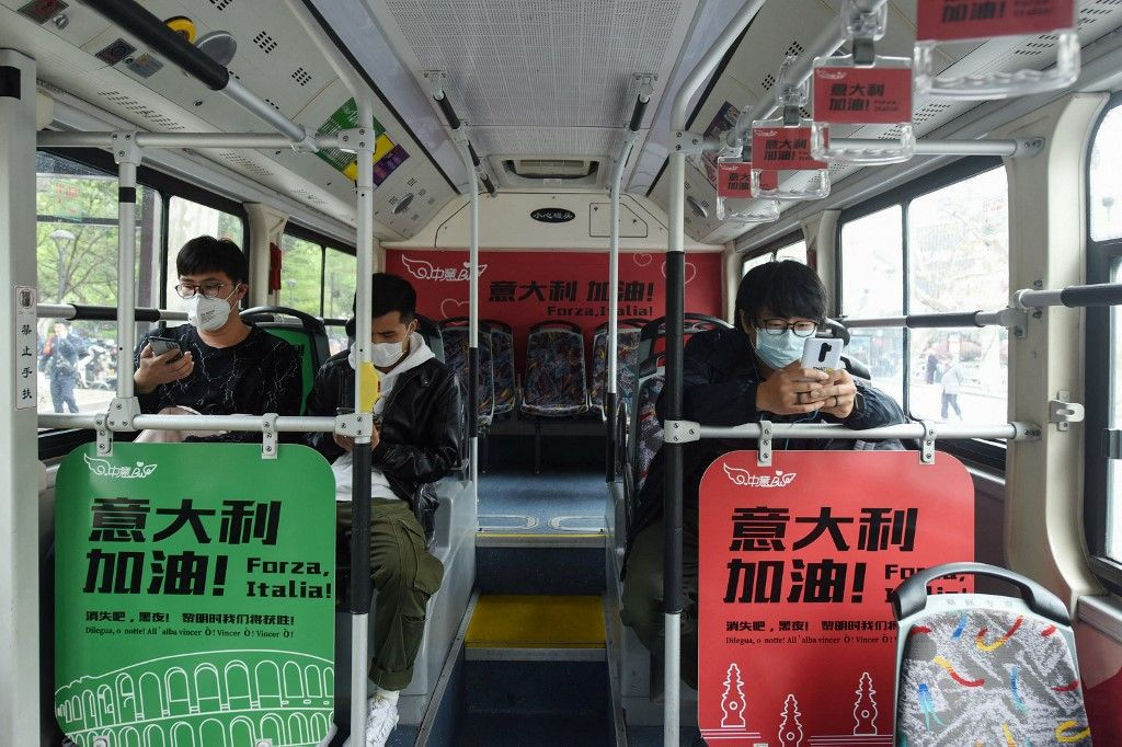 Des passagers portant des masques consultent leurs téléphones portables dans un bus à Hangzhou, dans la province chinoise du Zhejiang, dans l'est de la Chine, le 24 mars 2020.