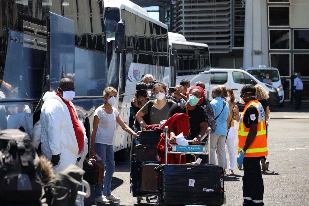 Des passagers qui viennent d'arriver de Paris attendent de monter à bord d'un bus de service spécial les emmenant dans une installation de quarantaine à La Réunion, à Saint-Denis.