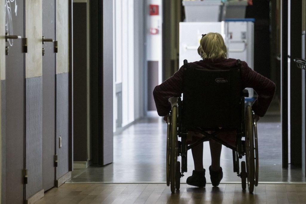 Une résidente d'un EHPAD dans l'est de la France se déplace en fauteuil roulant le 14 avril 2020 au cours du 29e jour d'un confinement strict en France face à la menace du Covid-19.