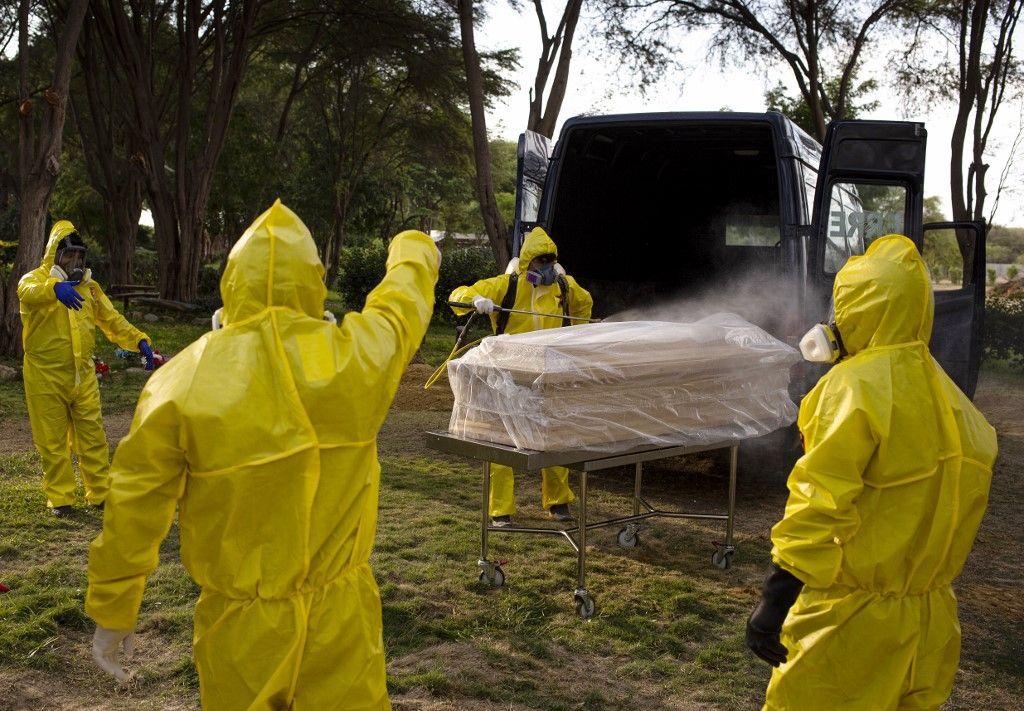 Des équipes appliquent un protocole sanitaire strict face au Covid-19 avant d'inhumer une victime de la pandémie.