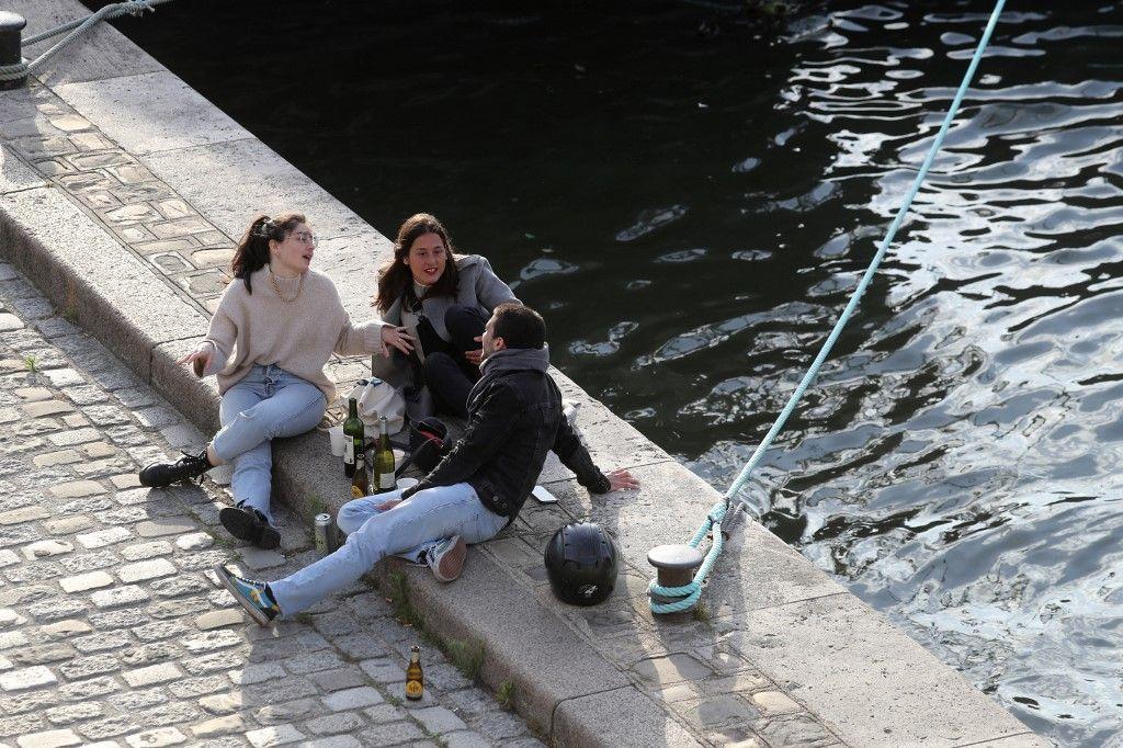 Des gens partagent un verre sur les rives de la Seine à Paris le 11 mai 2020, le premier jour de l'assouplissement des mesures liées au confinement pour tenter d'endiguer la pandémie de Covid-19.