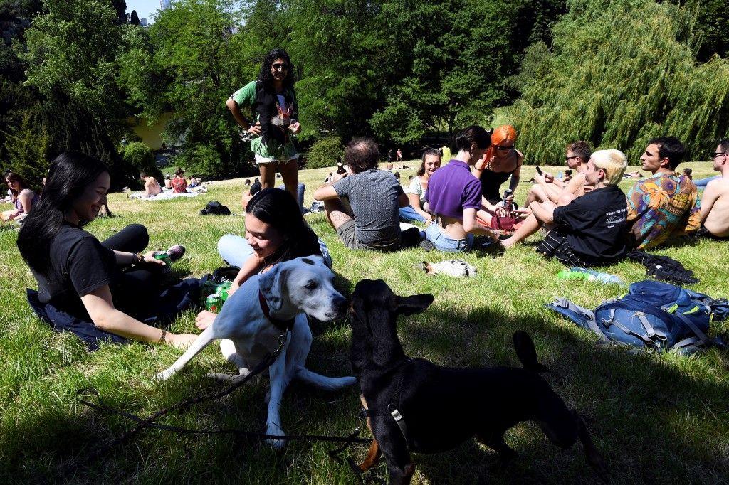 Des personnes profitent du soleil au parc des Buttes-Chaumont le 30 mai 2020 à Paris, le premier jour de sa réouverture, lors de l'assouplissement des restrictions sanitaires.