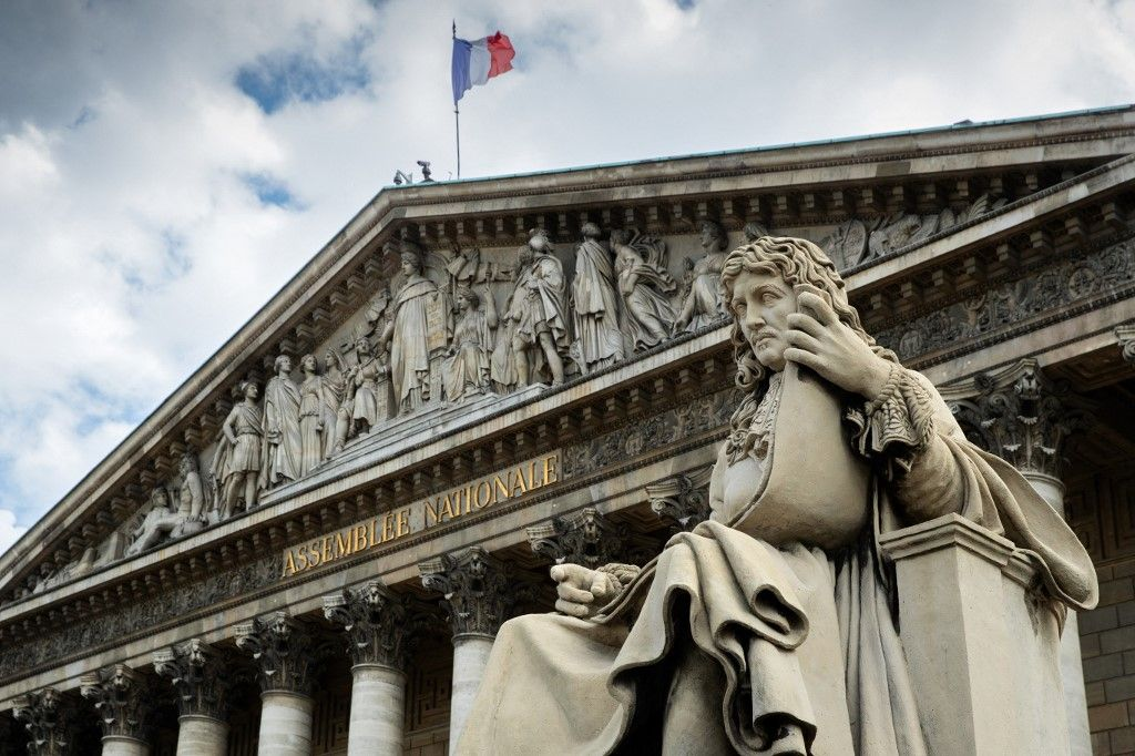 Une photo prise le 11 juin 2020 à Paris montre une statue de Jean-Baptiste Colbert et un drapeau français sur le frontispice du Palais Bourbon.