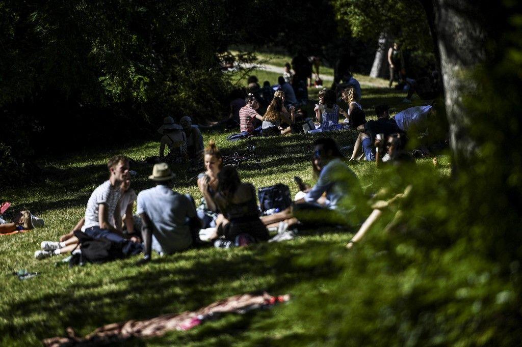 Des personnes profitent d'une journée ensoleillée pendant une vague de chaleur au Parc des Buttes Chaumont à Paris en juin 2020.