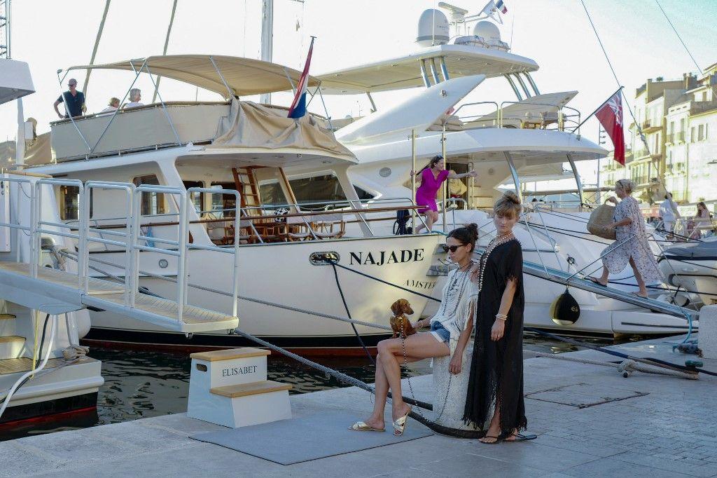 Des personnes se rassemblent près de yachts amarrés au port de Saint-Tropez, dans le sud de la France, le 5 juillet 2020.