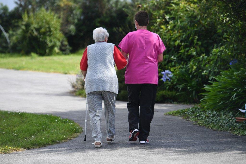 Une femme âgée, résidente d'un EHPAD à Ploudalmezeau, dans l'ouest de la France, se promène avec une infirmière, le 23 juillet 2020.