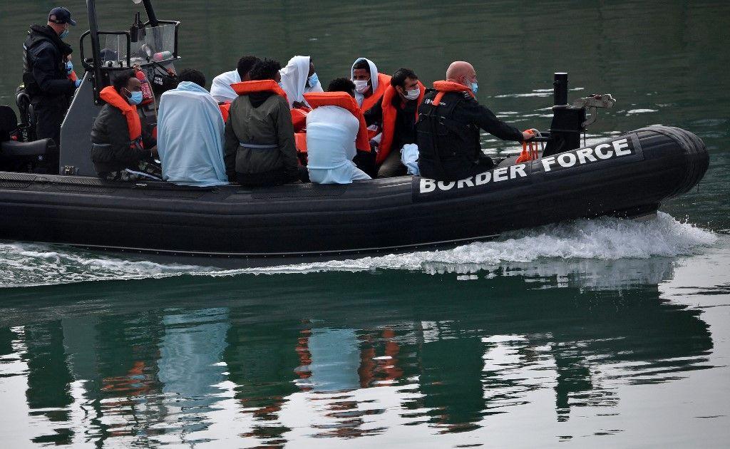 Des agents des forces frontalières britanniques accompagnent des migrants recueillis en mer lors de la traversée de la Manche, à Douvres, le 15 août 2020.