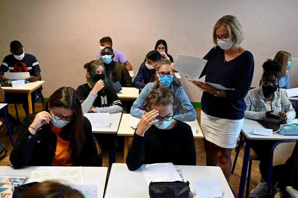 Une enseignante distribue des documents aux élèves d'une salle de classe d'un lycée à Rennes, le 1er septembre 2020.