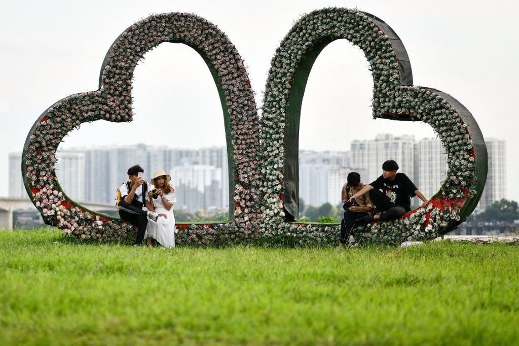 Des gens sont assis sur une structure en forme de cœur dans un champ ouvert le long des rives du fleuve Rouge à Hanoï le 13 septembre 2020.
