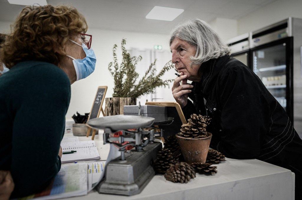 Sur cette photo prise le 9 septembre 2020, une patiente atteinte de la maladie d'Alzheimer discute avec un membre du personnel de l'épicerie d'un village landais, un site pour les patients atteints de la maladie d'Alzheimer à Dax.