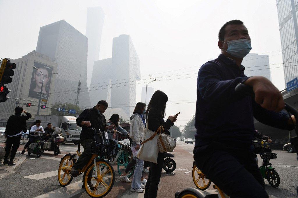 Des personnes attendent pour traverser une route, un jour pollué à Pékin, le 10 octobre 2020.