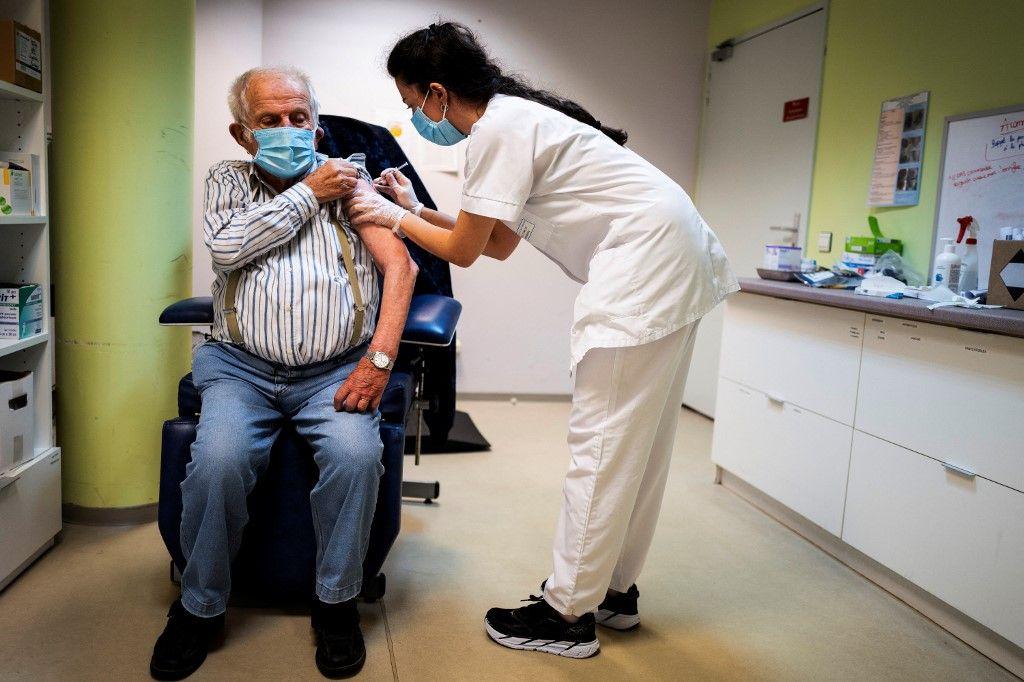 Une membre du personnel soignant vaccine un homme contre la Covid-19.