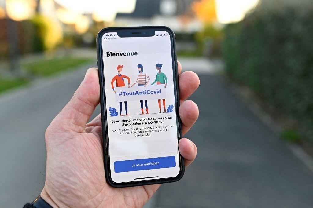 """Un homme utilise l'application """"TousAntiCovid"""" sur son smartphone."""