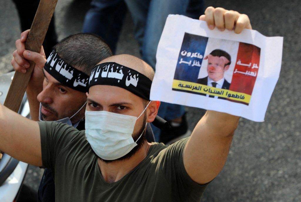 Un membre du parti islamiste radical libanais Tahrir lève une estampe montrant le drapeau national français avec une photo se moquant d'Emmanuel Macron, le 30 octobre 2020.