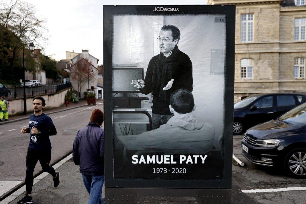 Des piétons passent devant une affiche représentant le professeur Samuel Paty, dans le centre-ville de Conflans-Sainte-Honorine.