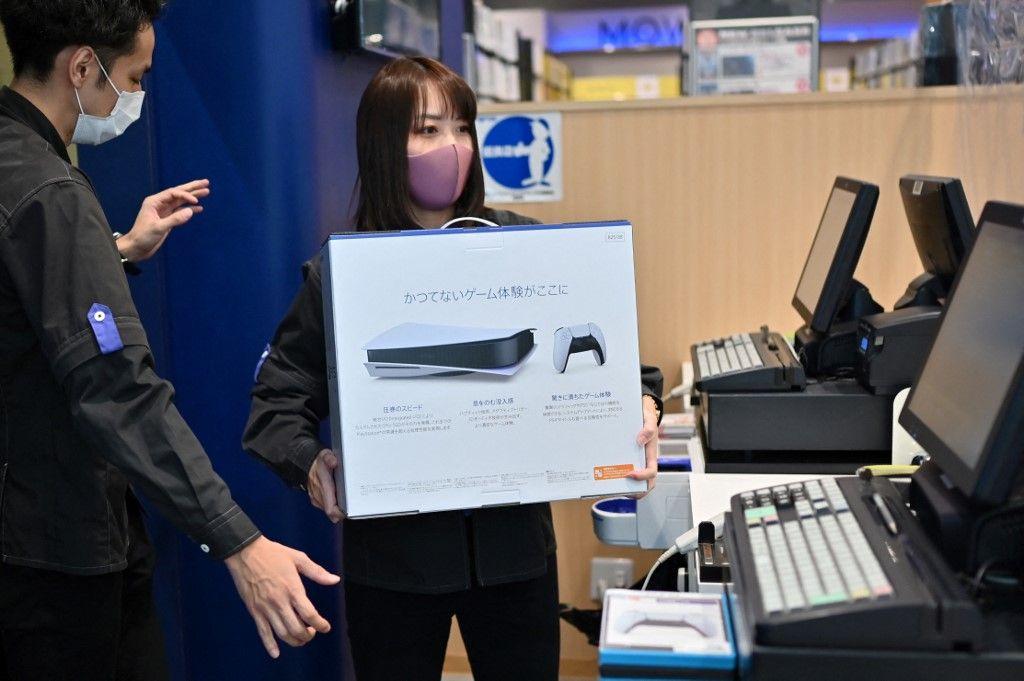 Un employé prépare la nouvelle console de jeu de Sony, la PlayStation 5, pour un client le premier jour de son lancement, dans un magasin à Kawasaki, au Japon, le 12 novembre 2020.