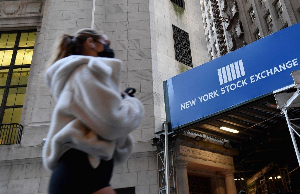 Une femme marchant devant la bourse de New York.
