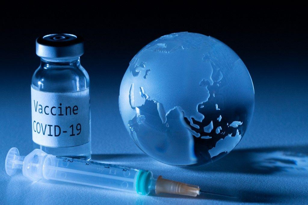 Une dose de vaccin contre la Covid-19 et un globe terrestre.