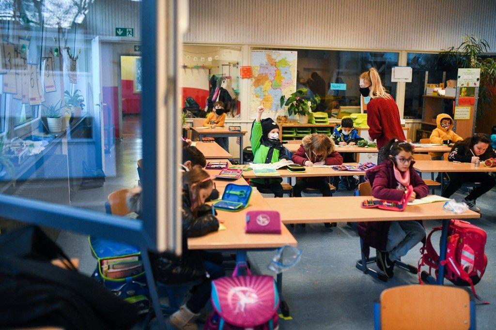 Des élèves portent travaillent dans leur classe avec la fenêtre ouverte à l'école primaire Petri de Dortmund, dans l'ouest de l'Allemagne, le 24 novembre 2020.