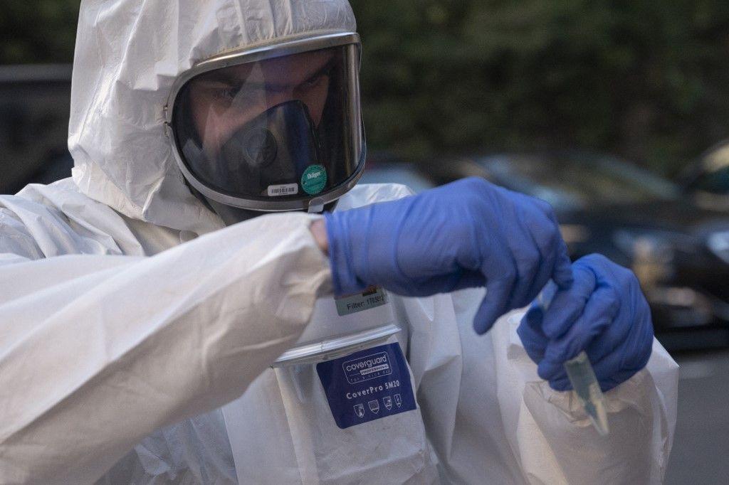 Un membre des Marins-Pompiers de Marseille détient un échantillon d'eaux usées pour détecter la présence de la Covid-19 à l'extérieur d'une maison de retraite à Marseille en janvier 2021.