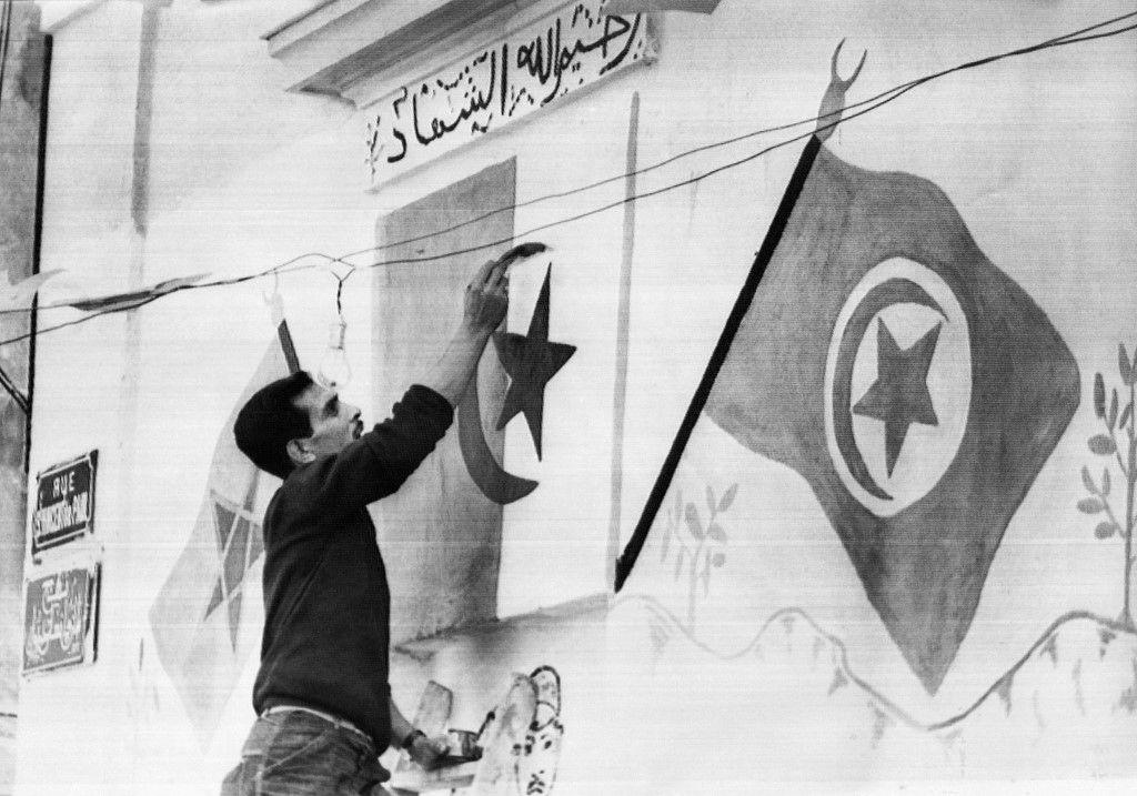 Un membre algérien du FLN représente des drapeaux algériens le 29 juin 1962 dans la casbah d'Alger avant le référendum d'autodétermination de l'Algérie.