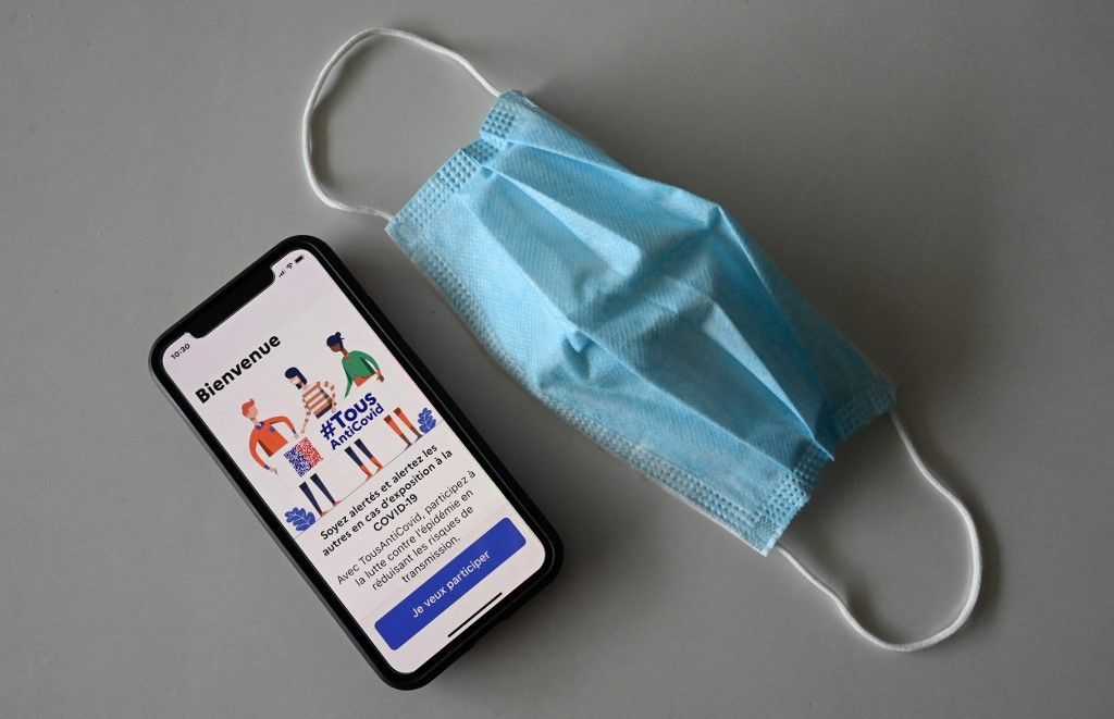 Un masque de protection et un téléphone portable connecté à l'application de traçage TousAntiCovid.