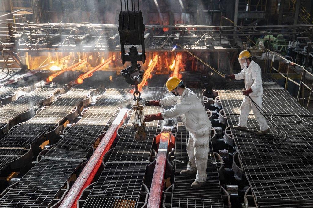 Des ouvriers fabriquent des barres de fer dans une usine sidérurgique à Lianyungang, dans la province chinoise du Jiangsu, dans l'est de la Chine, le 12 février 2021.