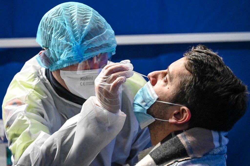 Un membre du personnel soignant effectue un prélèvement nasal sur un homme pour effectuer un test Covid-19 dans un centre de test du palais des congrès de Dunkerque, le 23 février 2021.