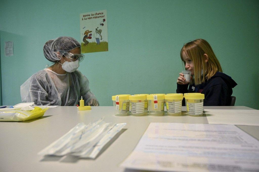 Un enfant donne un échantillon pour un test salivaire lors d'une visite du ministre de l'Education dans l'est de la France, lors du déploiement d'une campagne de test salivaire en mars 2021.