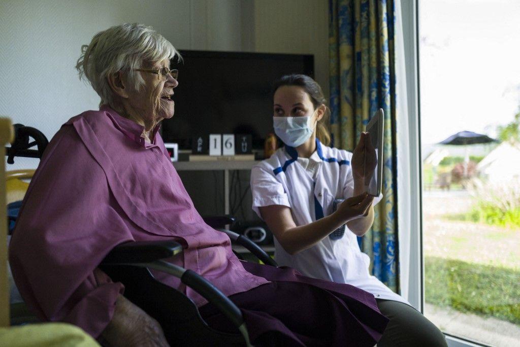 Une membre du personnel soignant auprès d'une résidente dans un EHPAD.