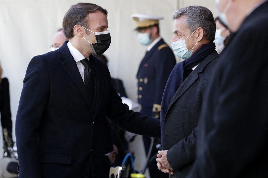 Le président Emmanuel Macron salue l'ancien président Nicolas Sarkozy avant une cérémonie d'hommage aux victimes du terrorisme au monument des Invalides à Paris, le 11 mars 2021.
